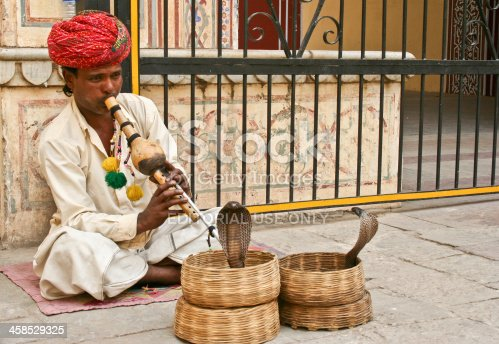 Jaipur, India - April 8, 2006: snake charmer with his flute and two cobras in their baskets