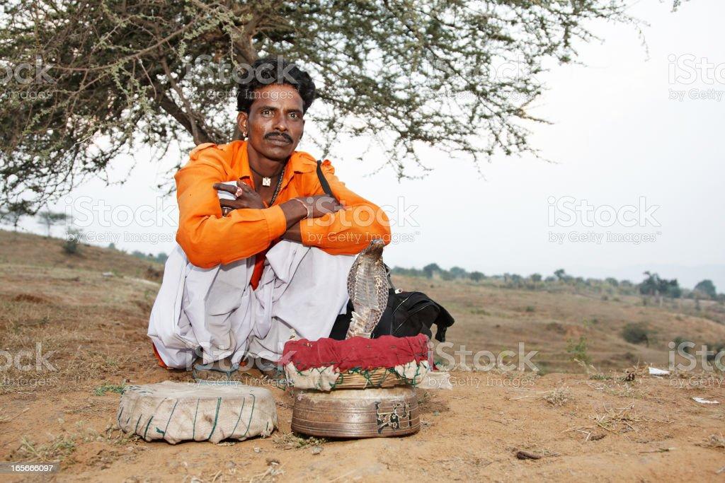 Snake charmer under desert tree royalty-free stock photo