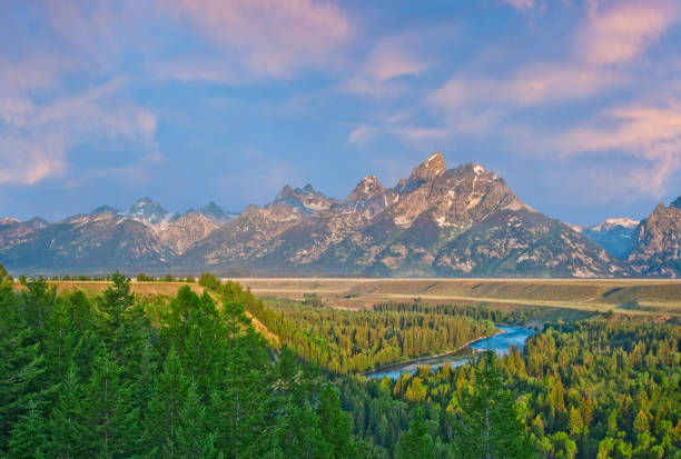 Snake River and the Teton Range at First Light The Snake River Overlook is the spot where Ansel Adams took his iconic photograph of the Snake River winding its way below the Teton Range. The scene pictured here was photographed just after sunrise, capturing the glow on the mountains. The Snake River Overlook is nine miles north of Moose Junction in Grand Teton National Park near Jackson, Wyoming, USA. jeff goulden stock pictures, royalty-free photos & images