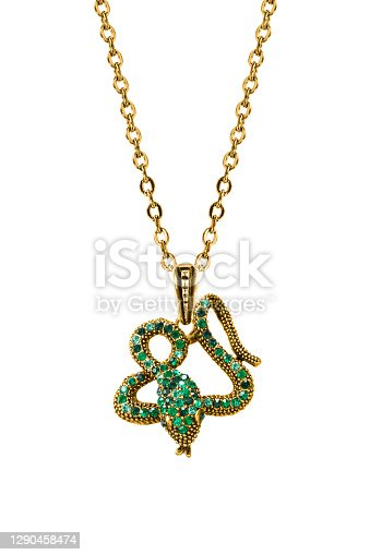 Gold pendant in the shape of a snake with green gems hanging on a chain on white background