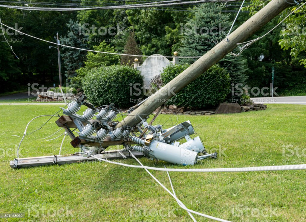 Snapped and downed power post and line after storm stock photo