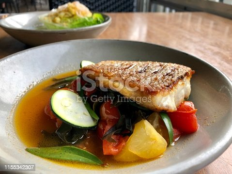 Closeup of a sauted fillet of snapper with zucchini slices, tomatoes and turnip pieces on a plate on a wooden table in a restaurant