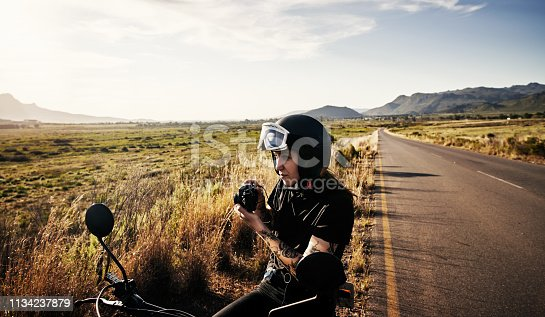Shot of a young woman riding her motorcycle through the countryside