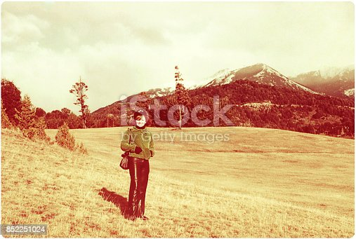 Vintage image of a woman in a winter location with snowy mountains on the background.