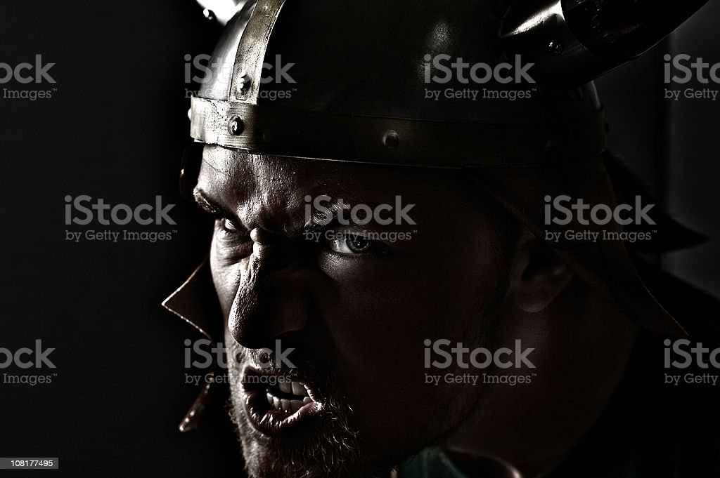 Snarling Man Wearing Viking Hat, Low Key stock photo