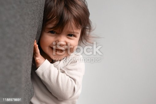 Excited little baby girl, playing in the house, hiding and smiling