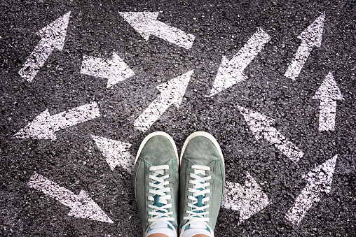 istock Sneaker shoes and arrows pointing in different directions on asphalt ground, choice concept 1136179001