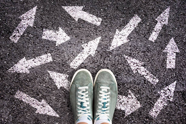 sneaker-schuhe und pfeile, die in verschiedene richtungen auf asphaltgrund zeigen, auswahlkonzept - jugendalter stock-fotos und bilder