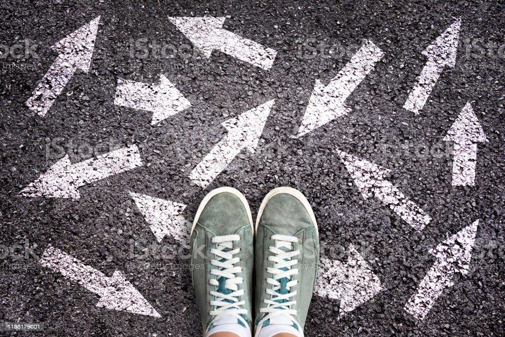 Sapatas e setas do sneaker que apontam em sentidos diferentes na terra de asfalto, conceito da escolha - foto de acervo