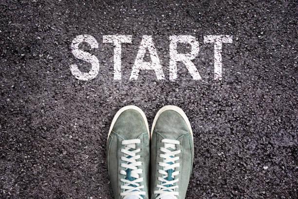 Sneaker-Schuhe und das Wort START auf Asphaltgrund geschrieben, neues Lebenskonzept – Foto