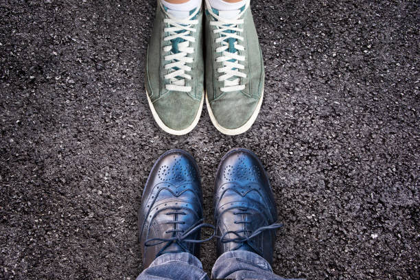 Sneakers and business shoes face to face on asphalt, work life balance concept stock photo
