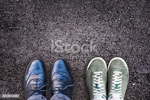 istock Sneakers and business shoes side by side on asphalt, work life balance concept 840830082