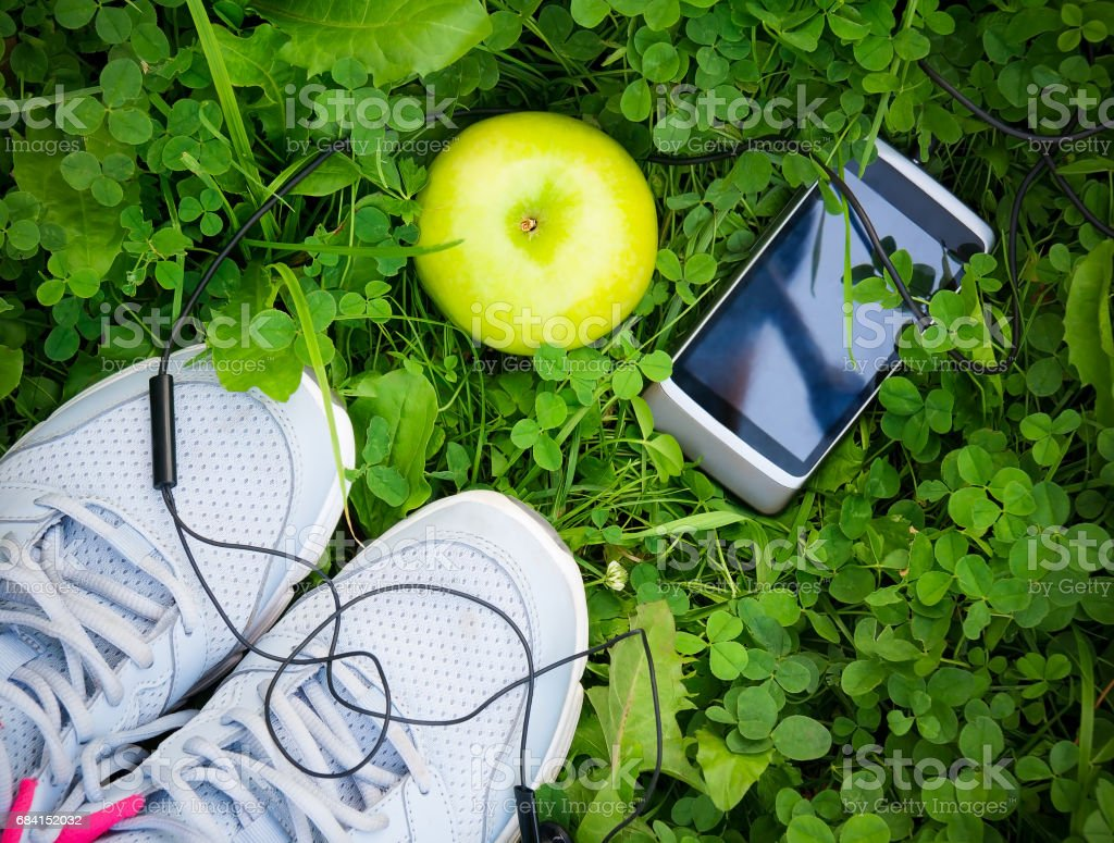 Sneakers and smartphone with headphones and apple foto stock royalty-free