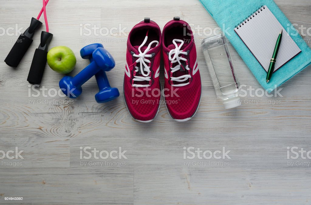 sneakers dumbbells bottle of water apple and measure tape Fitness concept with sneakers dumbbells bottle of water apple and measure tape on wooden table background   (0836) Aerobics Stock Photo