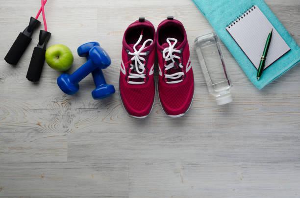 turnschuhe hanteln flasche wasser apfel und maßnahme band - trainingstagebuch stock-fotos und bilder
