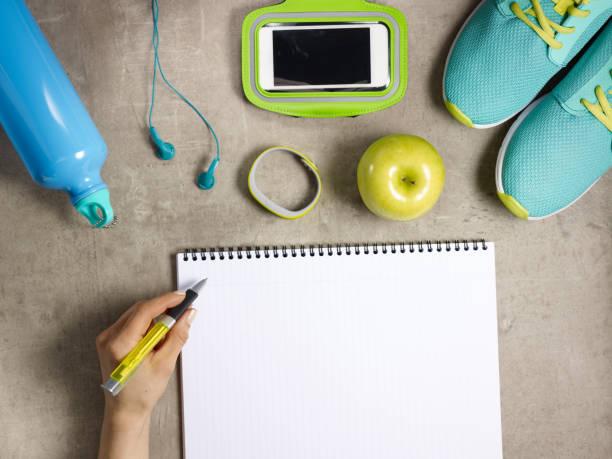 sneakers, fitness tracker och kvinnlig hand skrift i antecknings boken - calendar workout bildbanksfoton och bilder