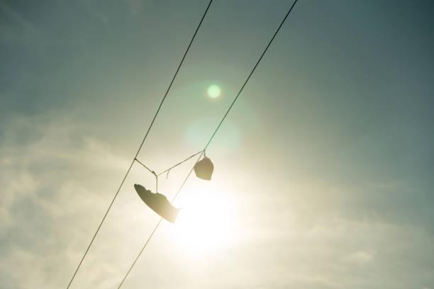 turnschuhe hängen an stromleitung drahtseil mit sonne und himmel im hintergrund. lustige urban outdoor-schuhe paar silhouette - kabelschuhe stock-fotos und bilder