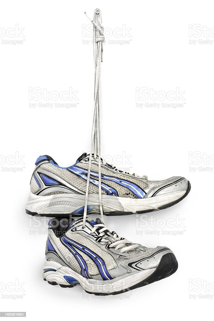 Sneakers hanging from a nail on white background stock photo