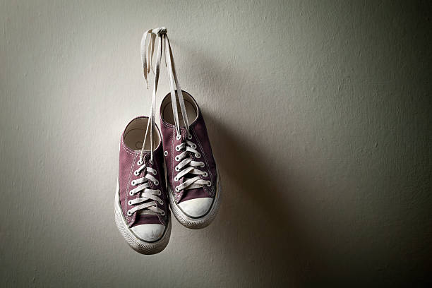 sneakers hanging on the wall - dirty shoes stock photos and pictures
