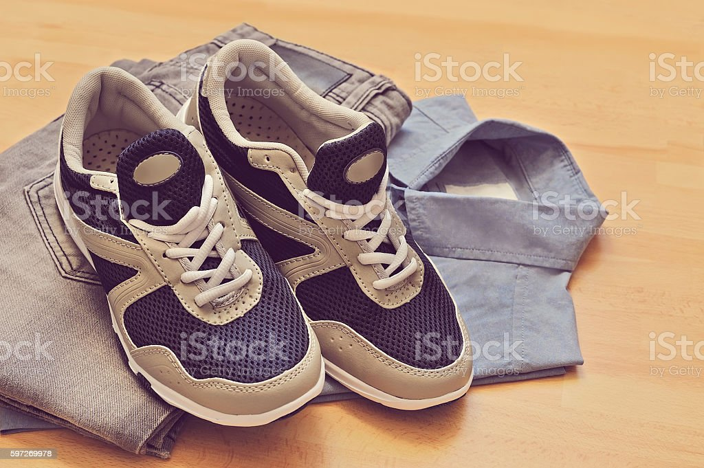 sneakers, jeans with shirt, on wooden background royalty-free stock photo
