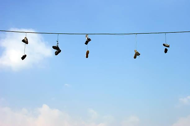 sneakers auf eine elektrische kabel - kabelschuhe stock-fotos und bilder