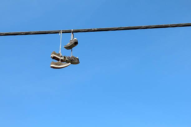 sneakers auf einem overhead wire - kabelschuhe stock-fotos und bilder