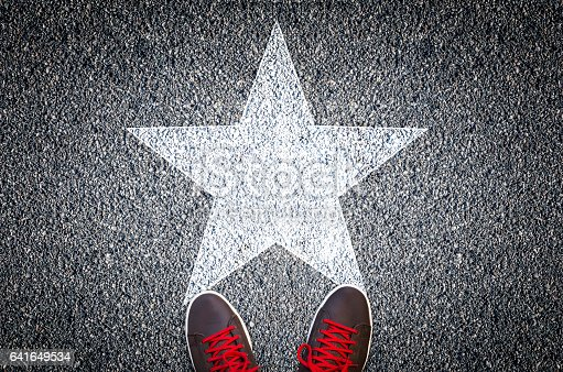 istock Sneakers on asphalt road with white star 641649534