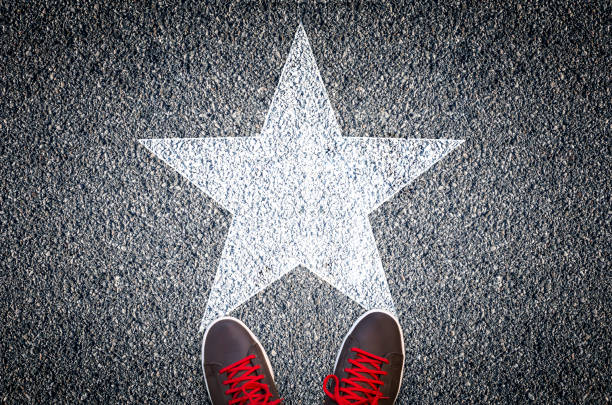 Sneakers on asphalt road with white star stock photo