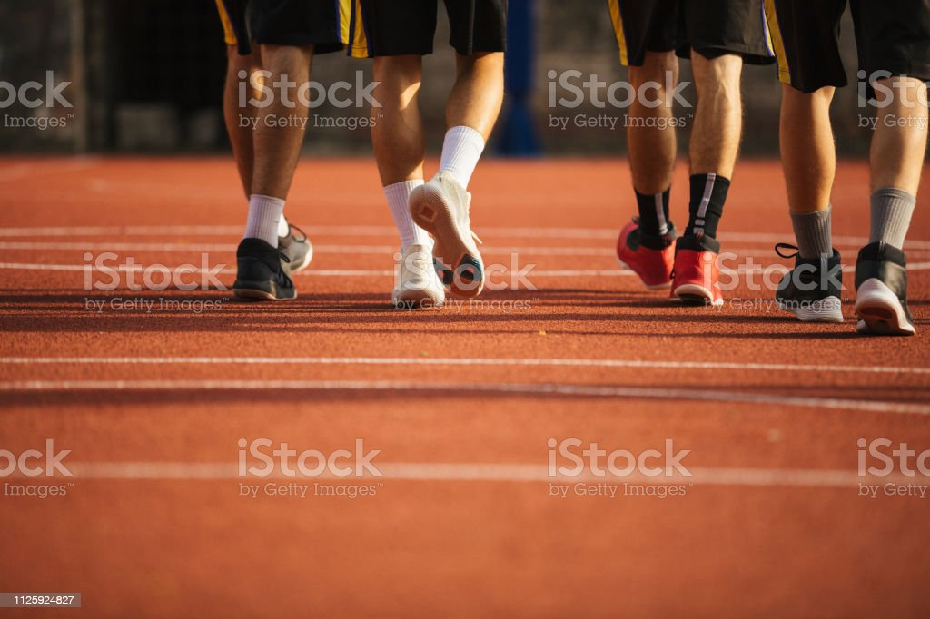 Low angle view of human legs in sport shoes, walking, unrecognizable...