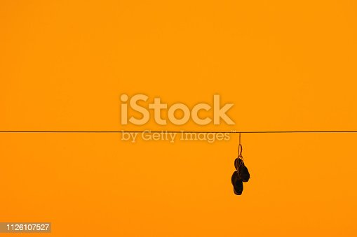 Sneakers hanging on electrical wire with golden sky background.