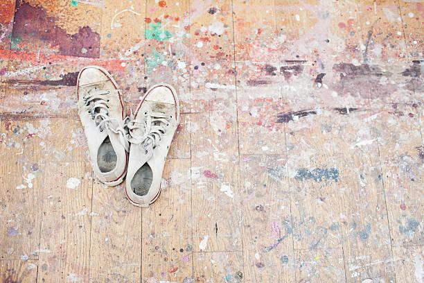 sneaker mit farbklecksen daraus holzboden - malerei schuhe stock-fotos und bilder