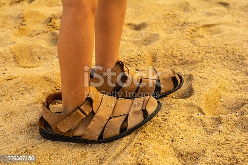 Warm summer. Children's feet, large leather sandals on the feet.