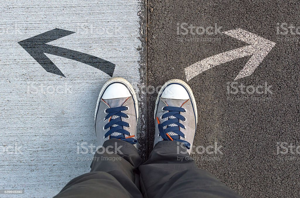 Sneakers standing on a road with arrows. stock photo