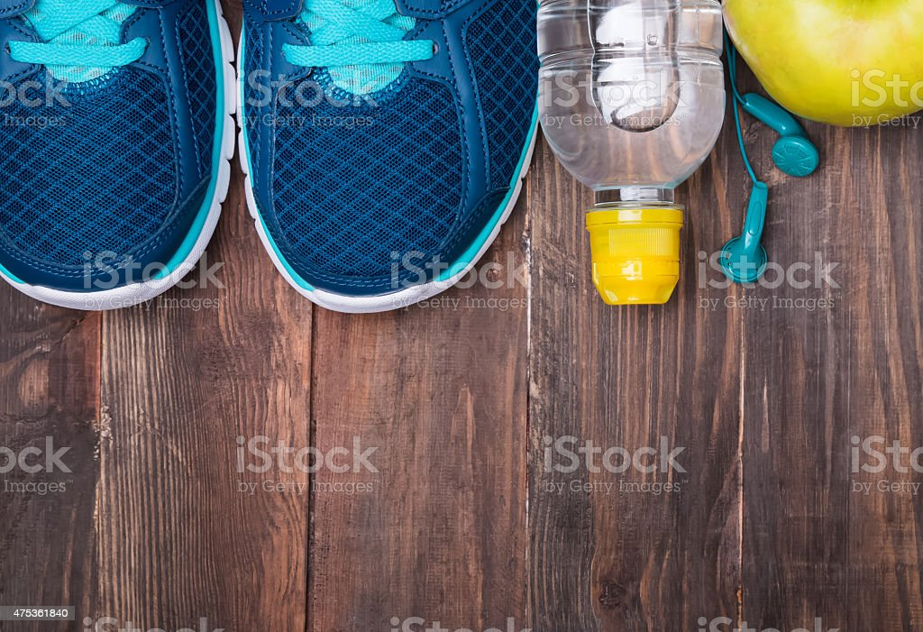 Sneakers, water, earphones  and apple on wooden background stock photo