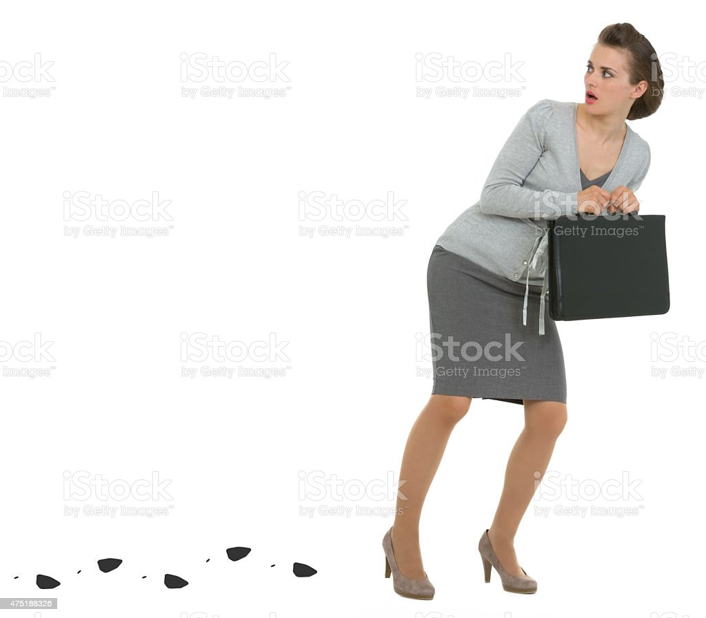 sneaking business woman with briefcase leaving trace stock photo