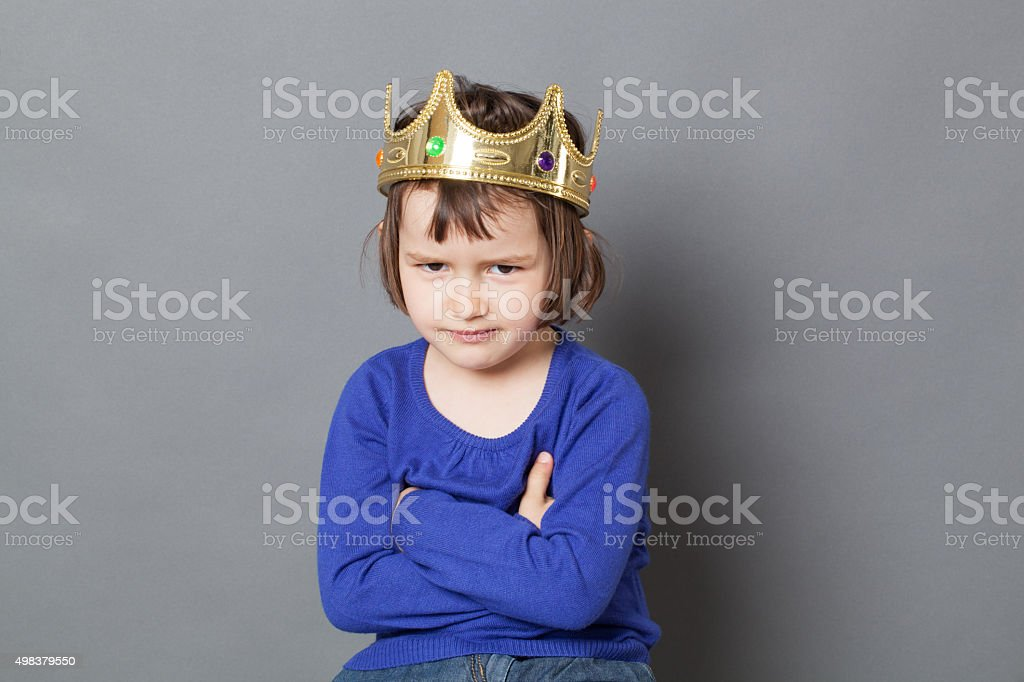 sneaky mollycoddled preschooler with arms folded for royal spoilt child stock photo