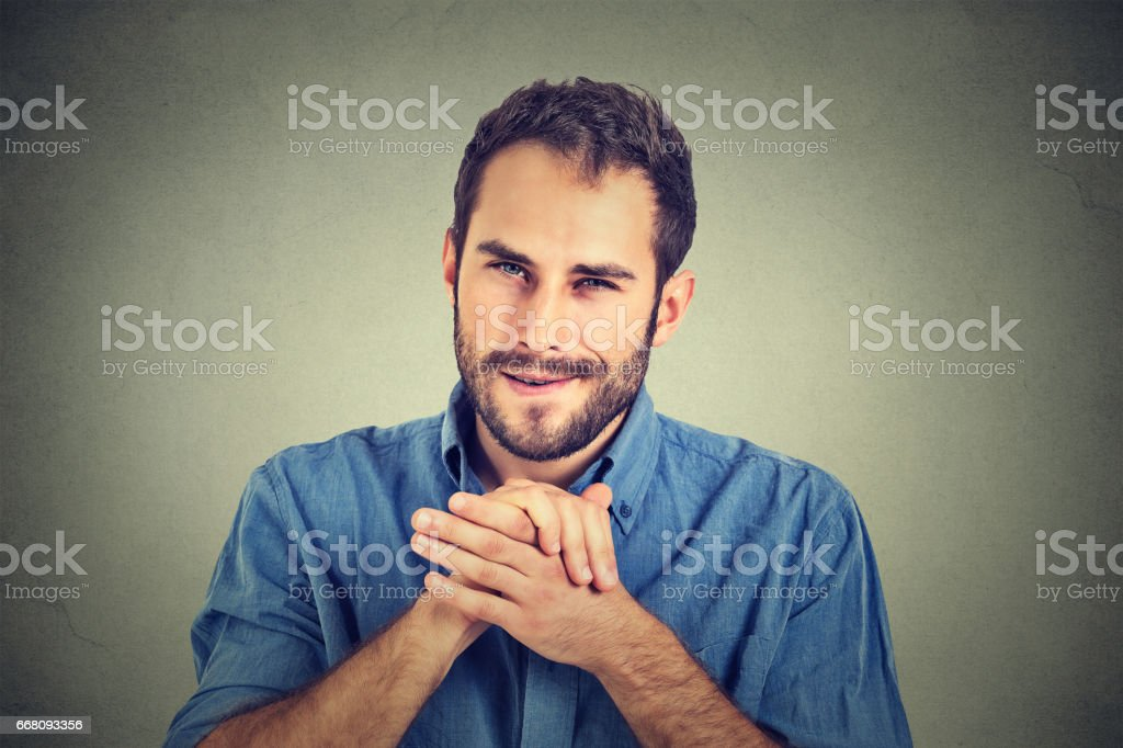 Sneaky scheming young man plotting something wants to screw someone stock photo