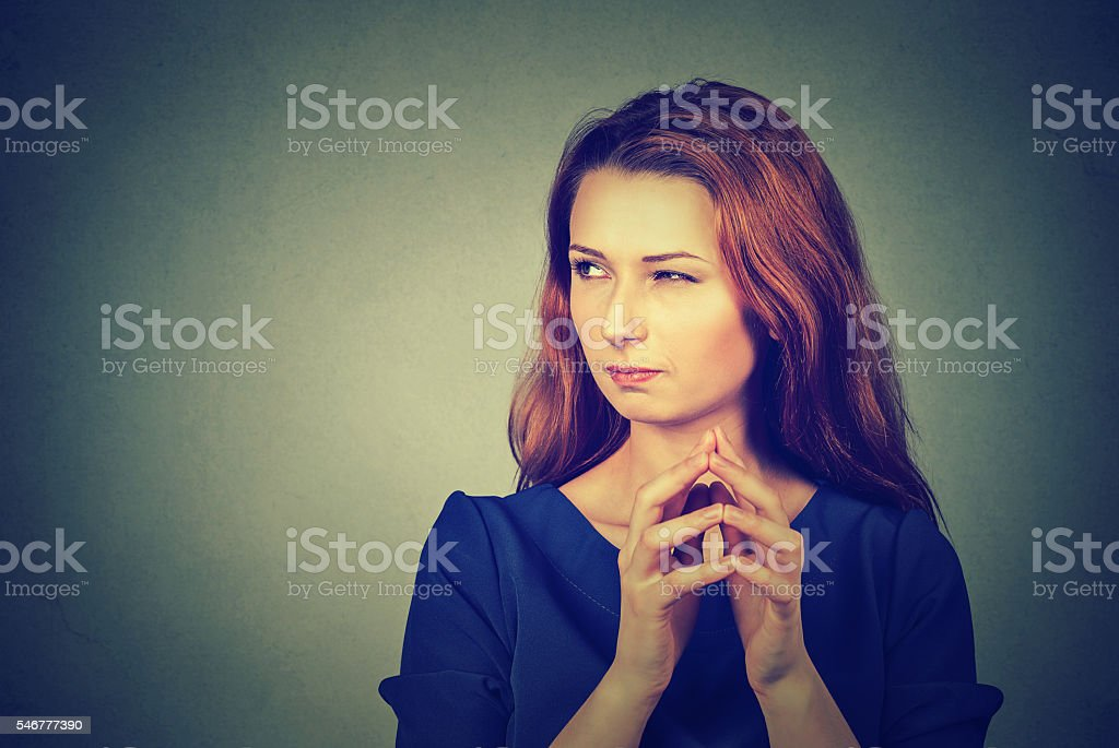 sneaky, sly, scheming young woman plotting something stock photo