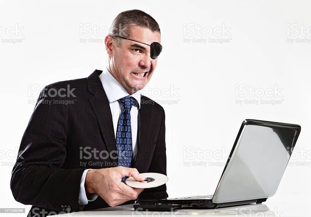 Sneering businessman in eye patch prepares to pirate software stock photo