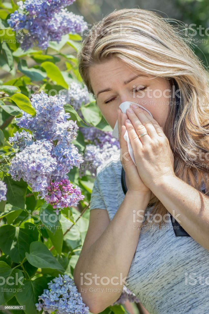 Allergic woman is blowing nose outdoor in nature