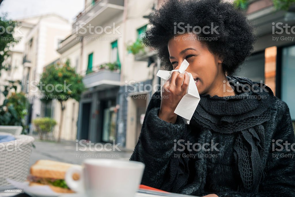 Sneezing due to flu during a break in a cafe stock photo