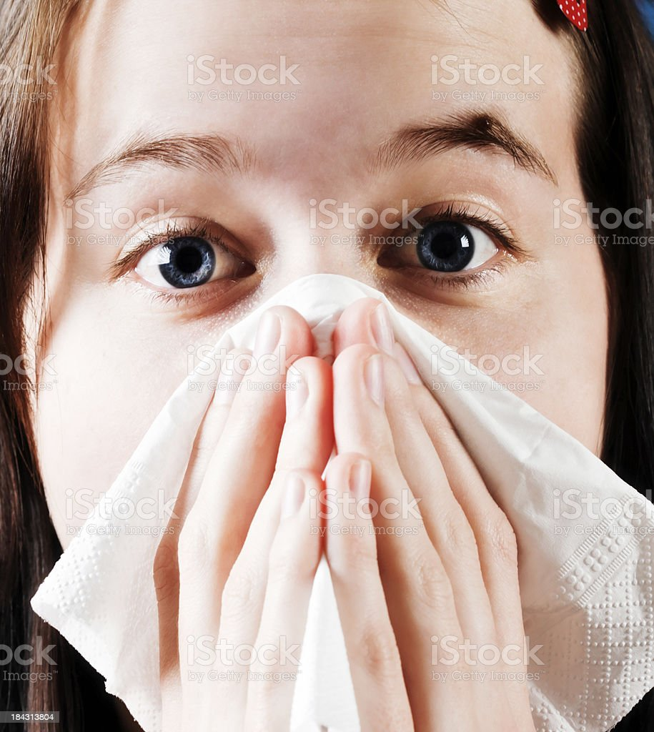 Sneezing or crying? Pretty brunette holds kleenex to nose royalty-free stock photo