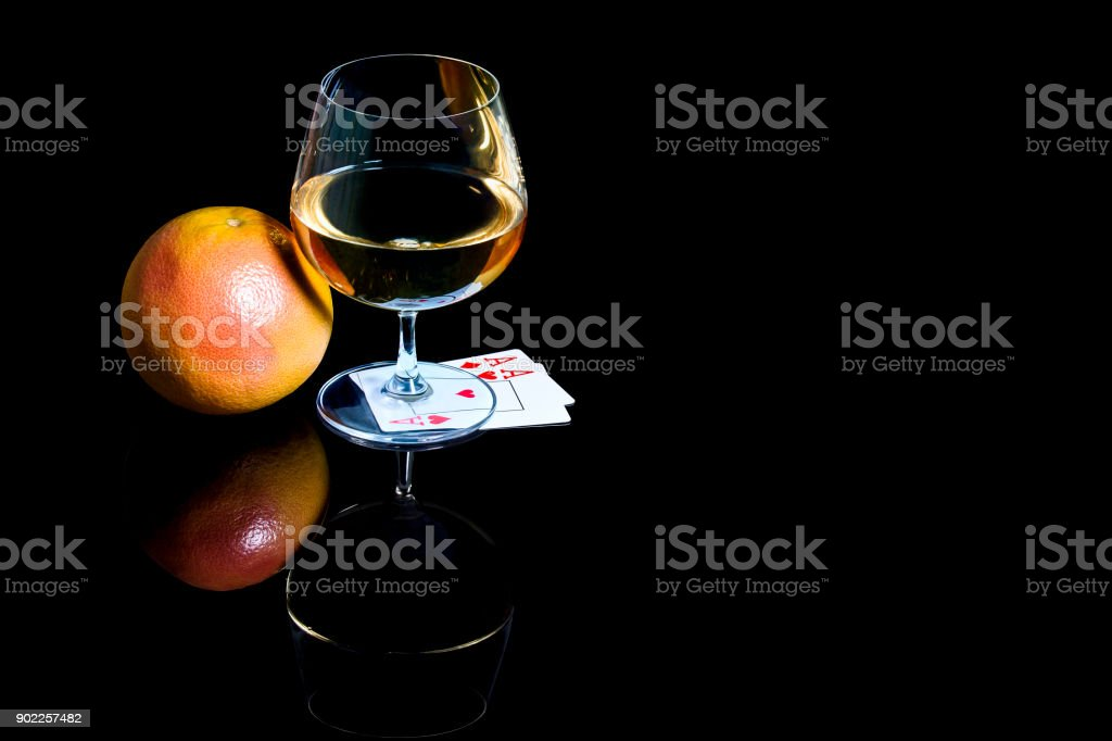 Snifter of brandy with playing cards and the grapefruit stock photo