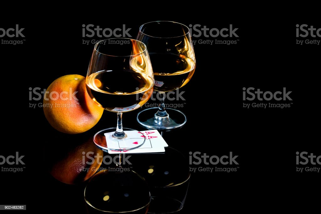 Snifters of brandy with playing cards and the grapefruit on the black background stock photo