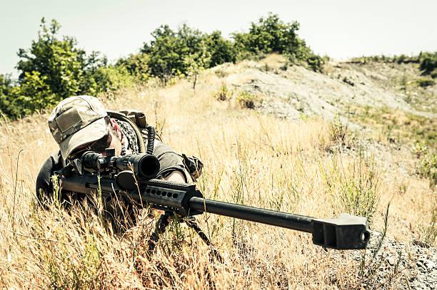 Sniper Aiming with Barrett M82A1 Precision Rifle in Arid Location stock photo