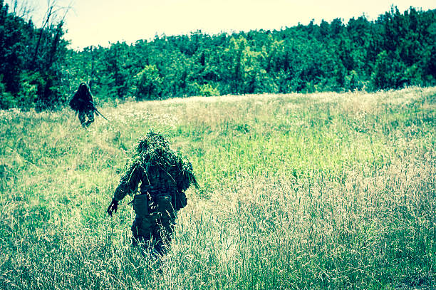 Sniper and Spotter Modern Soldiers Patrolling a Field Hiding stock photo