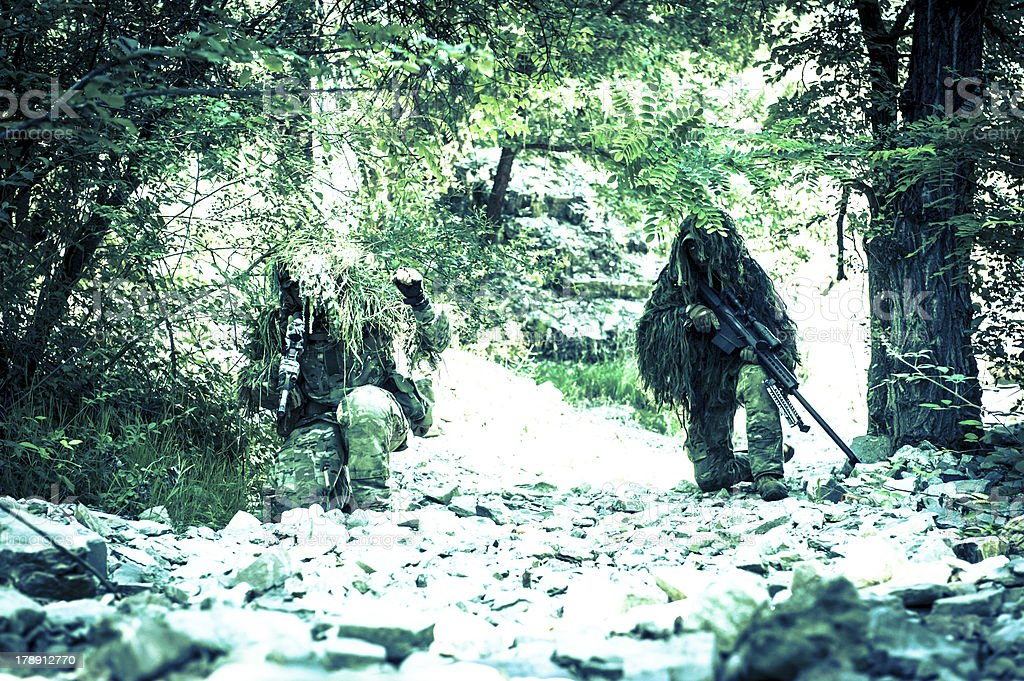 Sniper and Spotter Soldiers Hiding with Ghillie Suit Patrolling stock photo