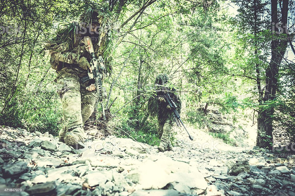 Sniper and Spotter Soldiers Hiding with Ghillie Suit Walking Alert stock photo