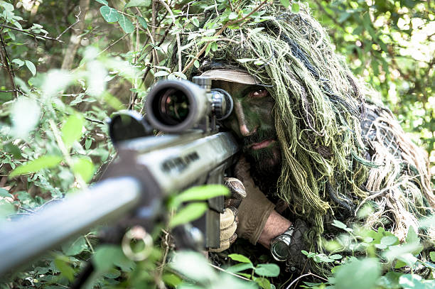Sniper Hiding in Ghillie Suit Aiming Barrett Precision Rifle stock photo