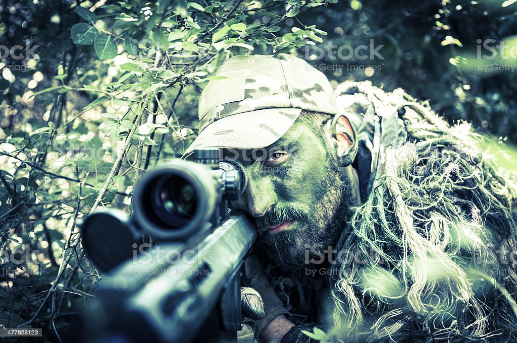 Sniper Hiding with Facial Camo and Ghillie Suit Aiming Rifle royalty-free stock photo